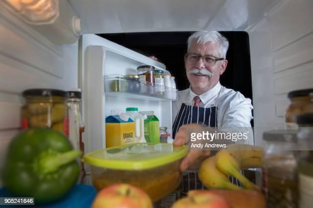 POV Man putting leftovers into a refrigerator