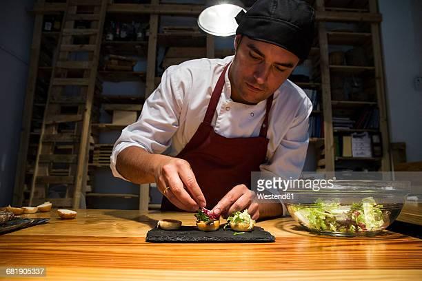 Man putting lettuce on mini hamburger buns