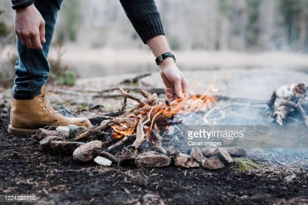 man putting logs on a handmade campfire outdoors in sweden - アウトドアファイヤー ストックフォトと画像
