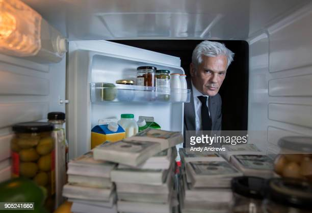 POV Man putting looking at stacks of US dollars in the fridge