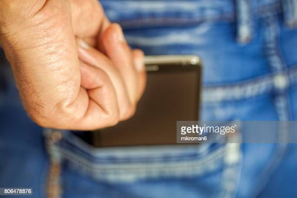 Man Putting Mobile phone Into Back Pocket blue jeans