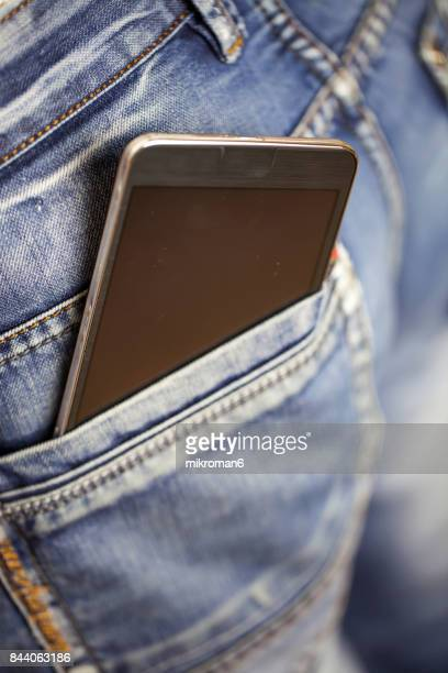 man putting mobile phone into back pocket blue jeans - pocket stock photos and pictures