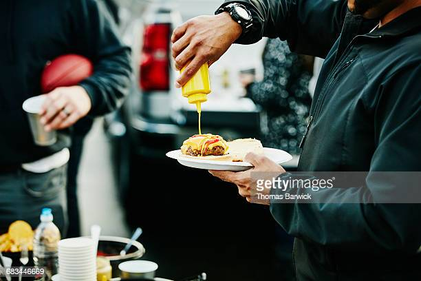 man putting mustard on burger at tailgating party - tailgate party stock pictures, royalty-free photos & images