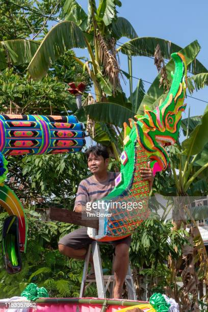 man putting naga head on parade float for rocket festival. - tim bewer stockfoto's en -beelden