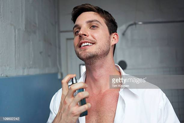 Man putting on cologne in urban loft bathroom
