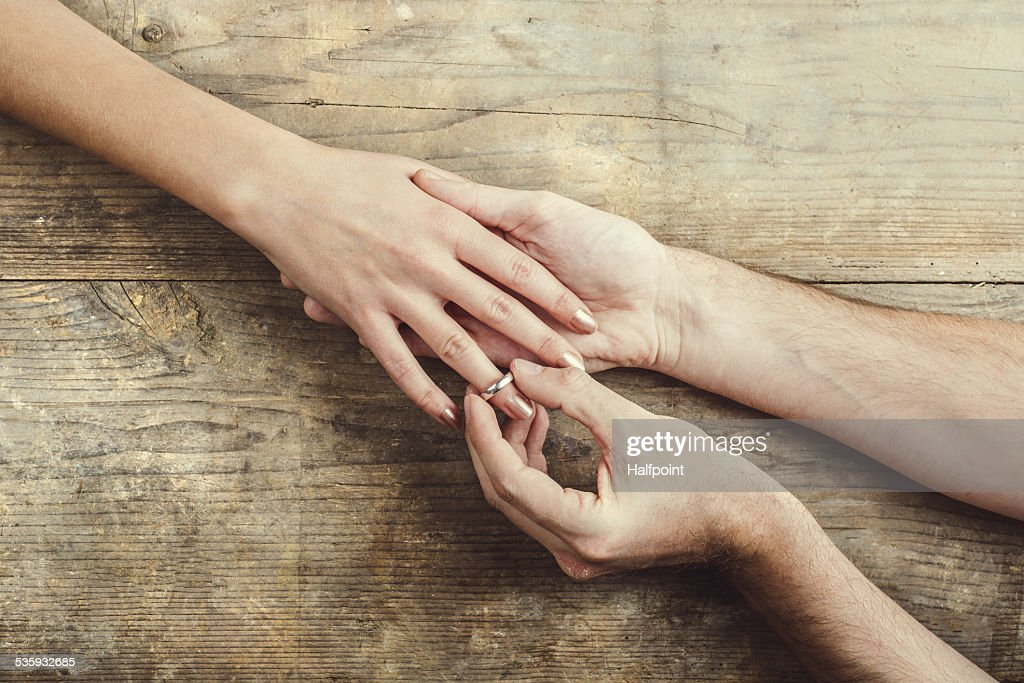 Man putting on engagement ring to his woman. : Stock Photo
