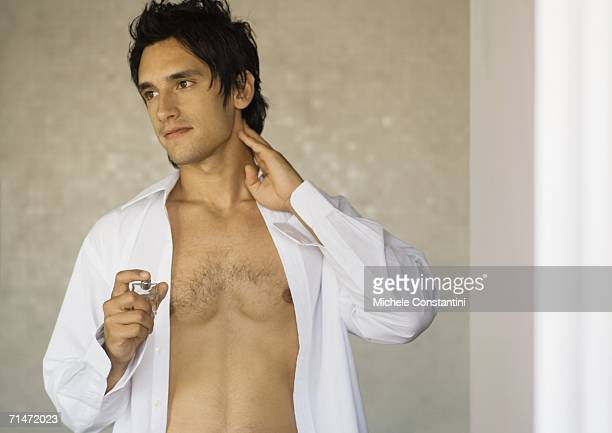 man putting on fragrance - hairy chest stock photos and pictures