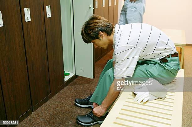 Man putting on his golf shoes