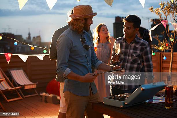 Man putting on music at early evening party