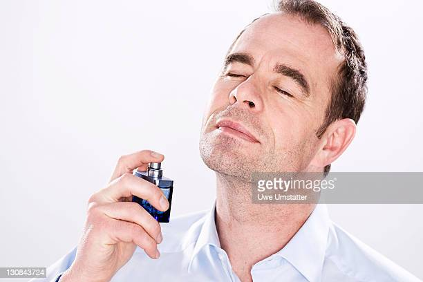 Man putting on perfume