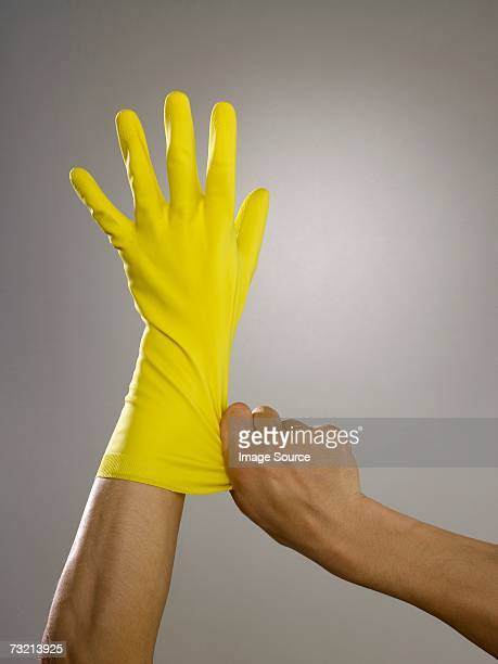 man putting on rubber glove - feticismo foto e immagini stock