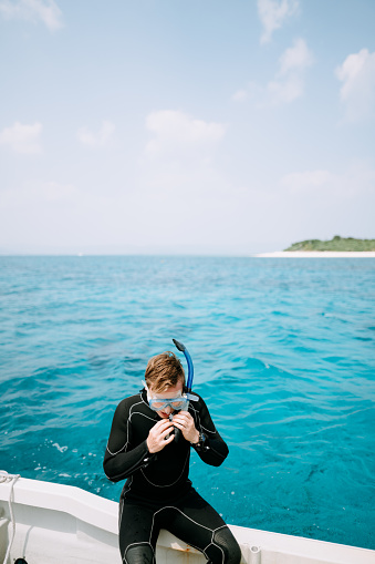Man putting on snorkel mask on boat around tropical island with blue water, Okinawa, Japan - gettyimageskorea