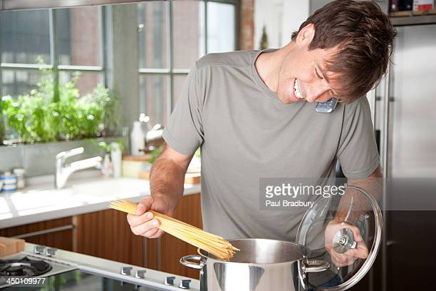 Man putting pasta into a cooking pot while on telephone