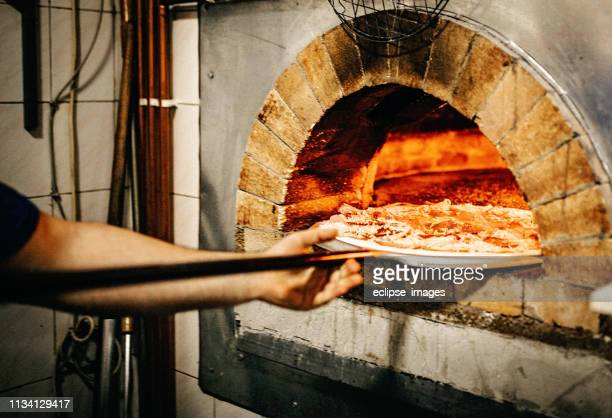 man putting pizza in oven - italy stock pictures, royalty-free photos & images