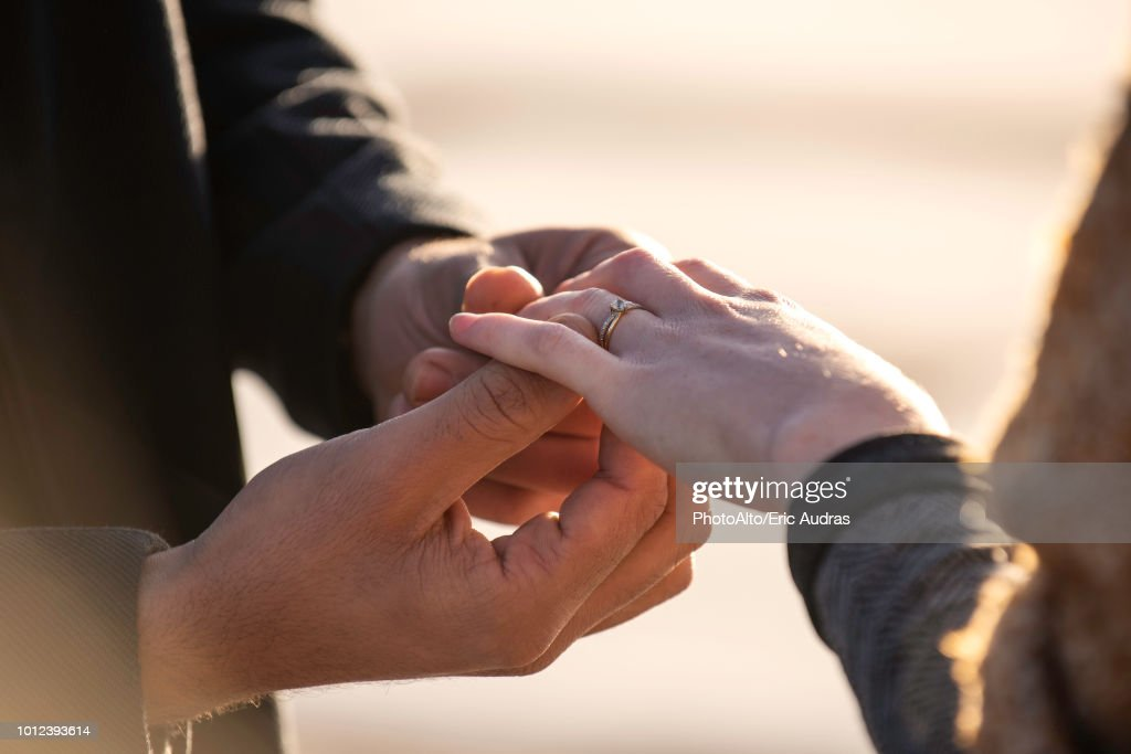 Man putting ring in his woman's finger : Stock Photo