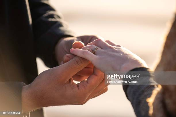 Man putting ring in his woman's finger