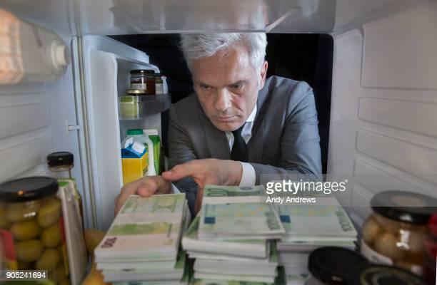 POV Man putting stacks of Euros into a fridge