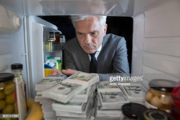 POV Man putting stacks of US dollars into a fridge