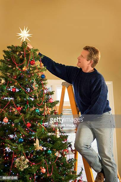 Man putting star on Christmas tree