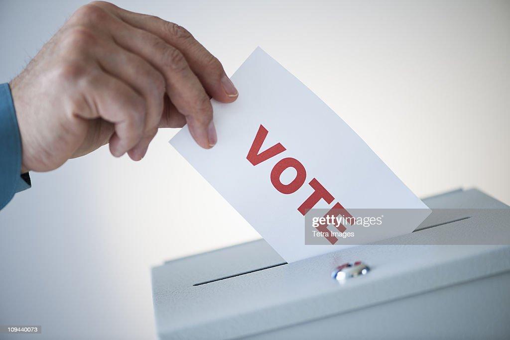 Man putting vote card into box : Stock Photo