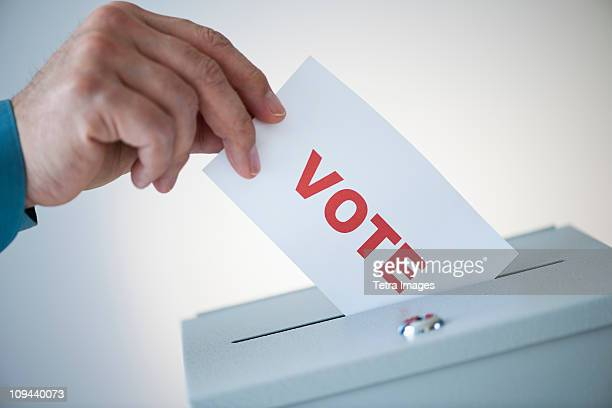 Man putting vote card into box