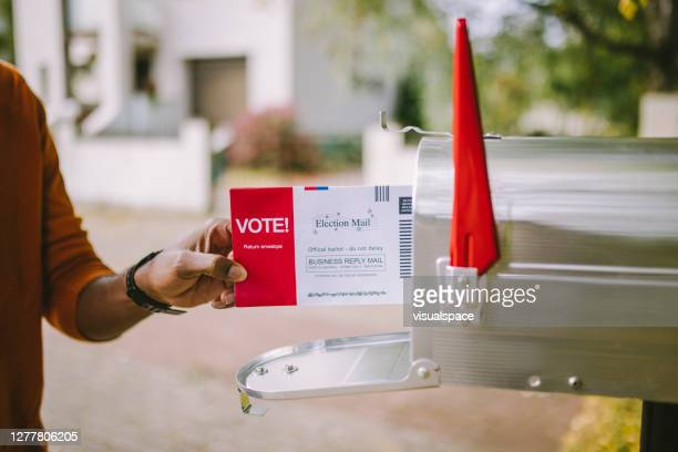 man putting voting ballot to mailbox. - voting by mail stock pictures, royalty-free photos & images