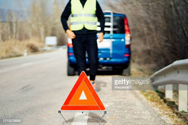 man putting warning triangle on country road by van breakdown - colliding stock pictures, royalty-free photos & images