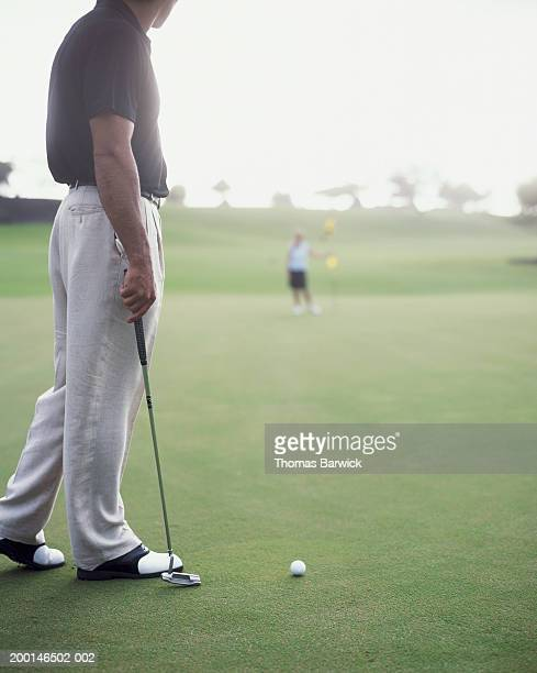 Man putting, woman holding golf flag in background (focus on man)
