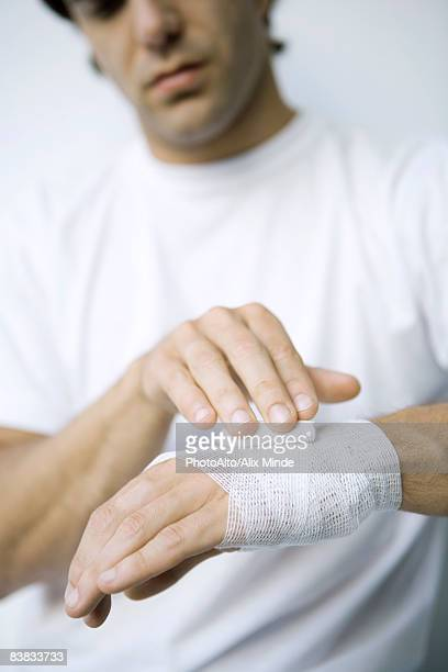 Man qrapping gauze around his wrist and hand, cropped view