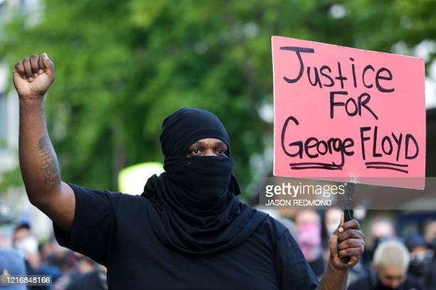 Man raise his fist and holds a placard during a protest for the death of George Floyd, in the Capitol Hill neighborhood of Seattle, Washington on...
