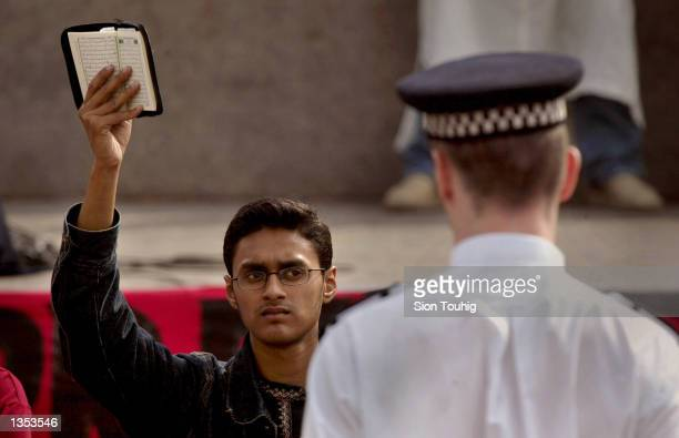A man raises a copy of the Q'uran in front of a British Police officer August 25 2002 during a 'Rally For Islam' demonstration held by AlMuhajiroun a...