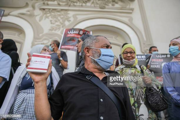 Man raises a copy of the Tunisian constitution during a demonstration held in Tunis, Tunisia, on September 11 to call for the release of the...