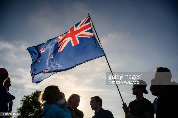A man raises a New Zealand flag as he attends a vigil in memory of the twin mosque massacre victims in Christchurch on March 24 2019 New Zealand will...