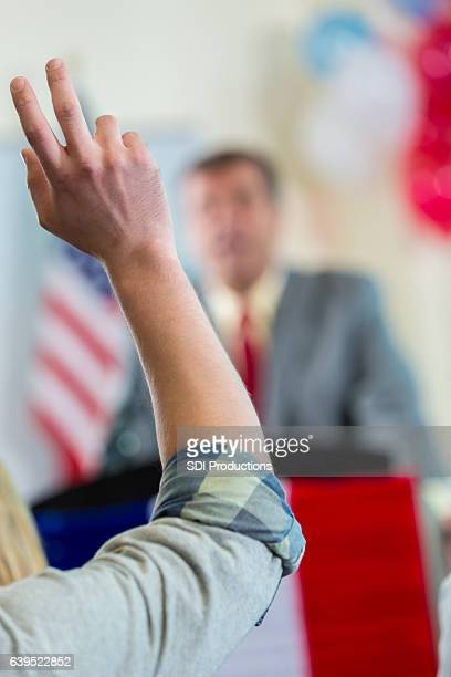 man raises hand to ask question during town hall meeting - town hall meeting stock photos and pictures