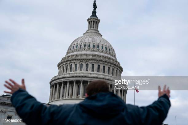 Man raises his arms as supporters of US President Donald Trump protest outside the US Capitol on January 6 in Washington, DC. - Donald Trump's...