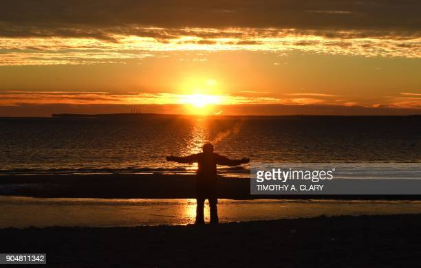 A man raises his arms in the very cold air as the sun comes up while taking a morning walk on the beach at Tod's Point Beach in Old Greenwich...