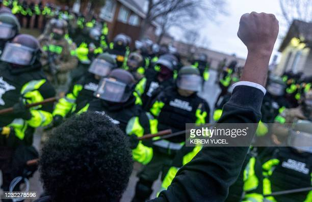 Man raises his fist as he faces the Minnesota State Troopers standing guard outside the Brooklyn Center Police Station after a police officer shot...