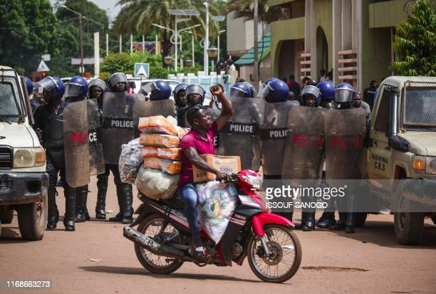 Man raises his fist as he rides a motorcycle past anti-riot police standing guard during a march called by the UAS union to call for better security...