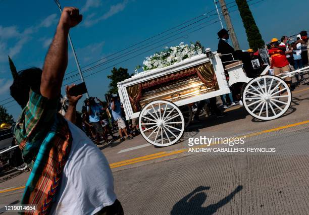TOPSHOT A man raises his fist as mourners watch the casket of George Floyd carried by a white horsedrawn carriage to his final resting place at the...