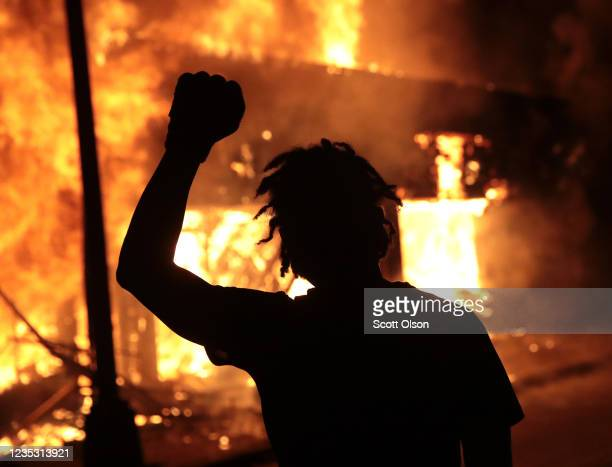 A man raises his fist in front of a burning building during protests sparked by the death of George Floyd while in police custody on May 29 2020 in...