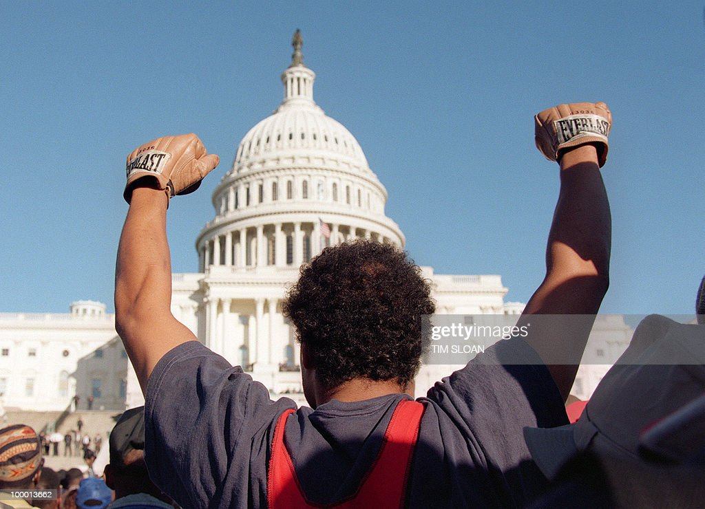A man raises his fists as he listens to the speech by Nation of Islam leader Louis Farrakhan at the Million Man March near the US Capitol, 16 October 1995, in Washington DC.