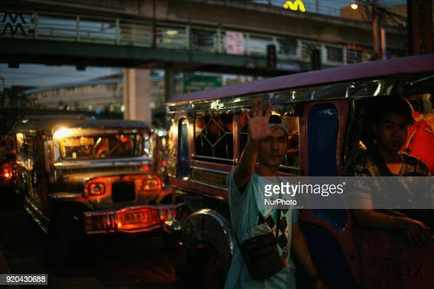 A man raises his hand as he flags potential jeepney passengers in Manila Philippines on Friday February 3 2018 The Jeepney has become a symbol of...