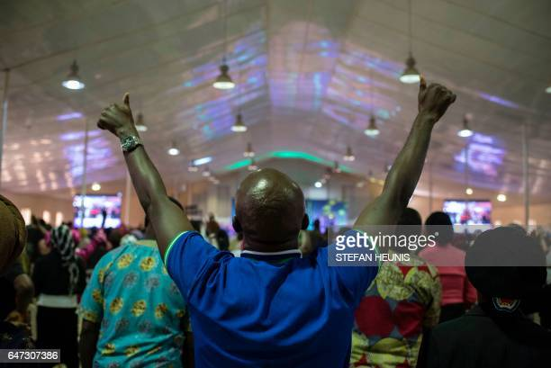 A man raises his hands during a prayer at the singles summit held at Prayer City on February 18 2017 The singles summit is one of a number of events...