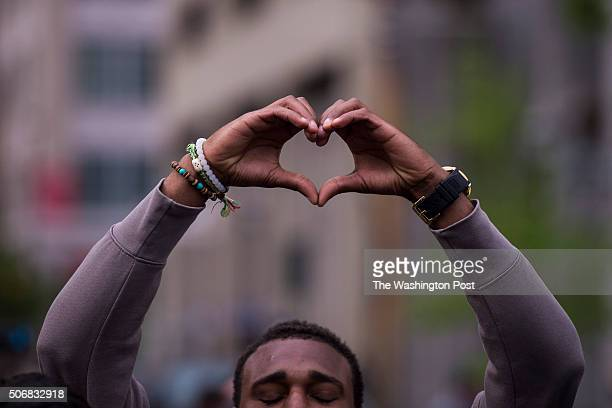 A man raises his hands to make a heart shape as he and other protestors march toward McKeldin Square near the Inner Harbor after it was announced...