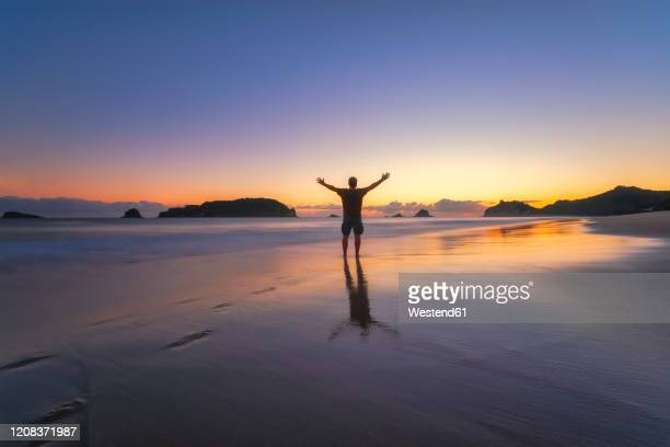 man raising arms at hahei beach during sunset, waikato, north island, new zealand - one man only stock pictures, royalty-free photos & images