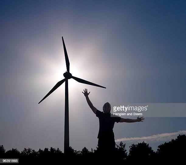 man raising arms at sun and Wind Turbine