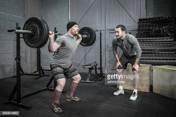 Man raising barbell with trainer motivation