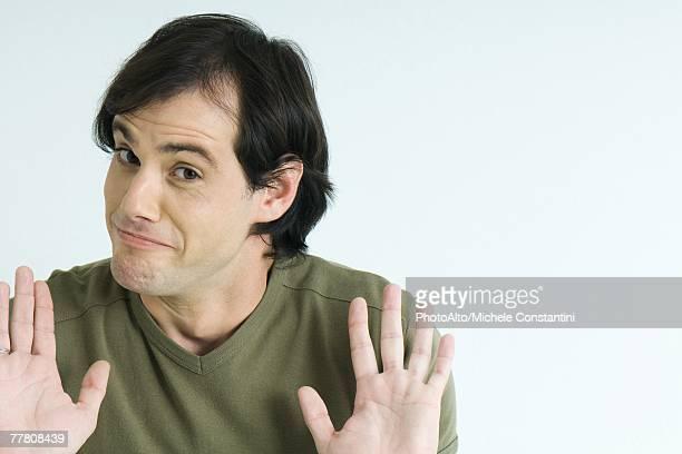 Man, raising eyebrows, holding up palms, portrait