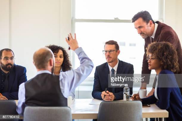 Man Raising Hand in Business Meeting