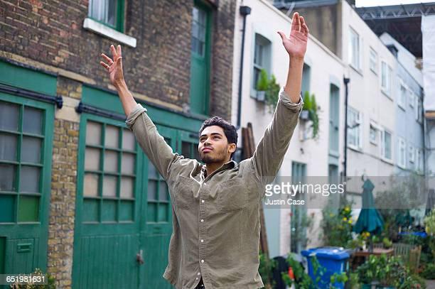 man raising his arms jubilating in his yard - arme hoch stock-fotos und bilder